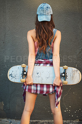 Buy stock photo Rearview shot of an unrecognizable young woman standing with a skateboard behind her back against a grey background