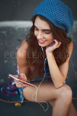 Buy stock photo Shot of a carefree young woman seated on the floor while listening to music through her earphones outside during the day