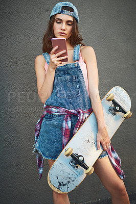 Buy stock photo Shot of an attractive young woman holding a skateboard while texting on her cellphone against a grey background