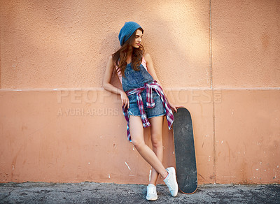 Buy stock photo Shot of a carefree young woman standing with her skateboard against a orange background