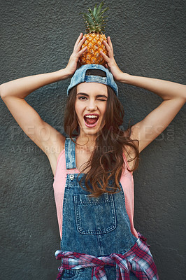 Buy stock photo Portrait of a cheerful young woman holding a pineapple on her head while standing against a grey background