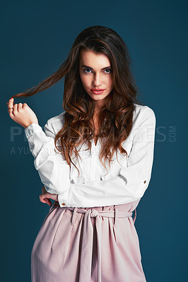 Buy stock photo Studio shot of an attractive young fashionable woman posing against a blue background