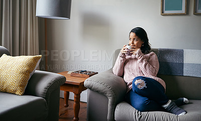 Buy stock photo Shot of an attractive young woman drinking coffee while relaxing at home