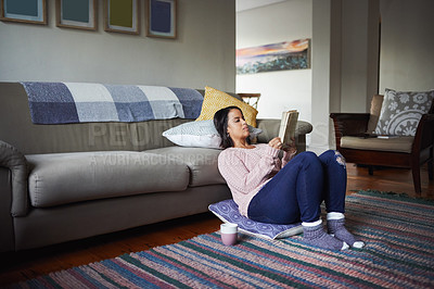 Buy stock photo Shot of an attractive young woman reading a book at home