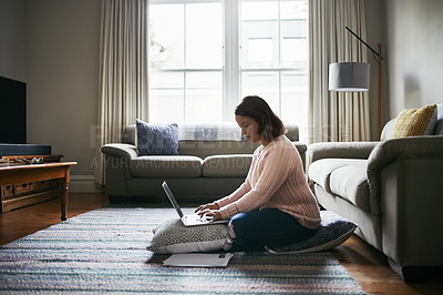 Buy stock photo Shot of an attractive young woman using a laptop while working from home