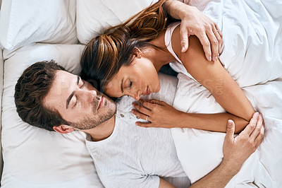Buy stock photo High angle shot of a loving young couple sleeping together at home