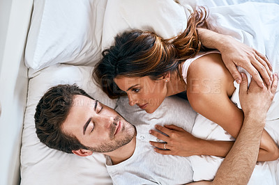 Buy stock photo High angle shot of a young woman watching her husband as he sleeps in bed at home