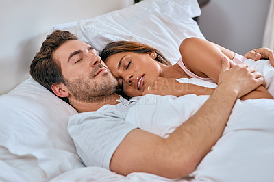 Buy stock photo Shot of a loving young couple sleeping together at home