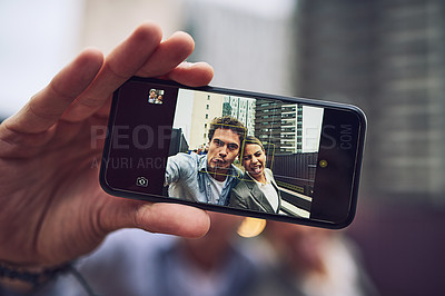 Buy stock photo Portrait of two cheerful young work colleagues taking a self portrait together outside during the day