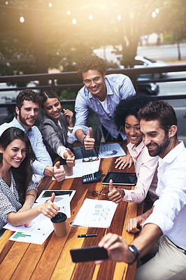 Buy stock photo Shot of a group of colleagues showing thumbs up while taking a selfie together outdoors