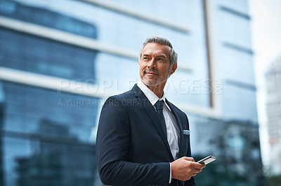 Buy stock photo Shot of a handsome mature businessman in corporate attire using a cellphone outside outside during the day