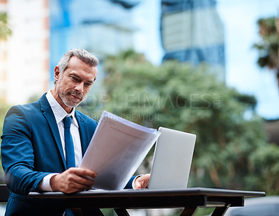 Buy stock photo Shot of a handsome mature businessman in corporate attire going over a document and using a laptop outside during the day