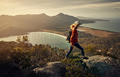 Buy stock photo Full length shot of a young woman hiking through the mountains