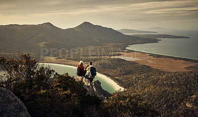Buy stock photo Rearview shot of a young couple taking in the view while sitting on a mountain peak