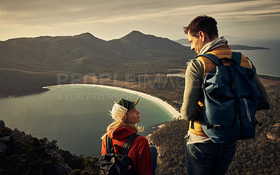Buy stock photo Rearview shot of a young couple taking in the view while resting on a mountain peak