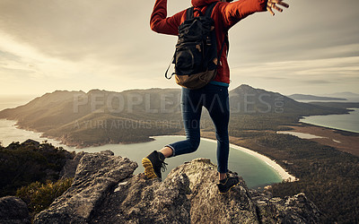 Buy stock photo Rearview shot of a young woman hiking through the mountains