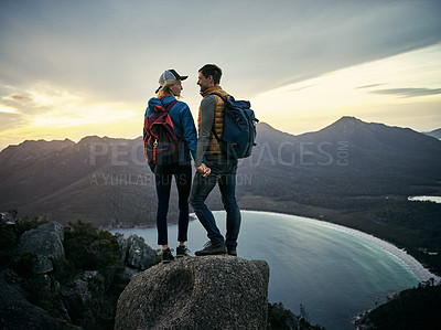 Buy stock photo Rearview shot of a young couple taking in the view while standing on a mountain peak