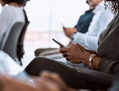 Buy stock photo Cropped shot of a group of businesspeople using their mobile phones during a conference