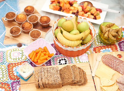 Buy stock photo Shot of a spread of different types of snacks placed together on a picnic blanket outside during the day