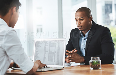 Buy stock photo Shot of two young businessmen having a discussion in a modern office