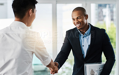 Buy stock photo Shot of two young businessmen shaking hands in a modern office