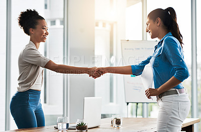 Buy stock photo Shot of two young businesswomen shaking hands in a modern office