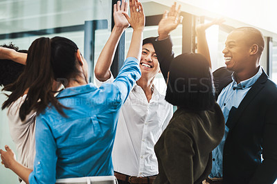 Buy stock photo Shot of a group of young businesspeople giving each other a high five in a modern office