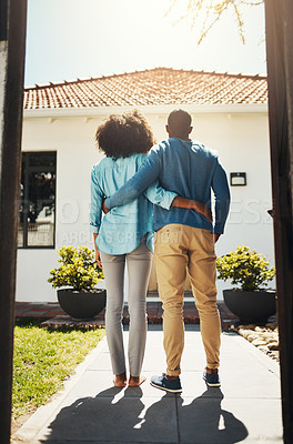 Buy stock photo Rearview shot of an unrecognizable couple holding each other while standing and looking at their new home
