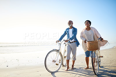 Buy stock photo Shot of a mature couple walking alongside their bikes at the beach