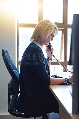 Buy stock photo Shot of a mature businesswoman talking on a telephone in an office