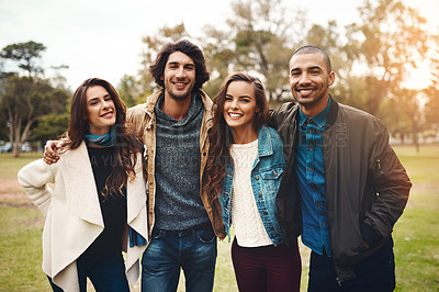 Buy stock photo Portrait of a group of cheerful young friends huddled together while standing in a park outside during the day