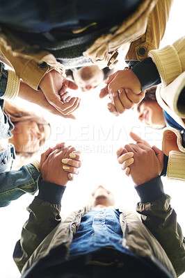 Buy stock photo Low angle portrait of a group of young friends huddled together while holding hands outside during the day
