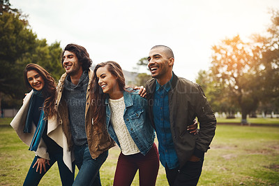 Buy stock photo Shot of a group of cheerful young friends huddled together while walking in a park outside during the day