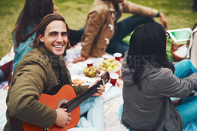 Buy stock photo Portrait of a cheerful young man about to play guitar at a picnic with his friends outside during the day