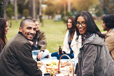 Buy stock photo Portrait of two cheerful young people seated at a picnic with friends outside during the day