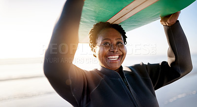 Buy stock photo Shot of a mature woman carrying a surfboard at the beach