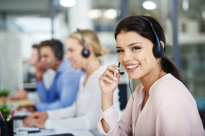 Buy stock photo Portrait of an attractive young woman working next to her team in a call center