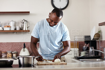 Buy stock photo Cropped shot of a young man listening to music while cooking in the kitchen at home
