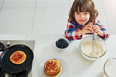 Buy stock photo High angle shot of an adorable little boy making pancakes in the kitchen at home