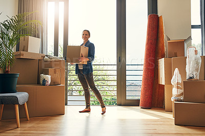 Buy stock photo Portrait of a cheerful middle aged woman holding a box while moving into her new home inside during the day