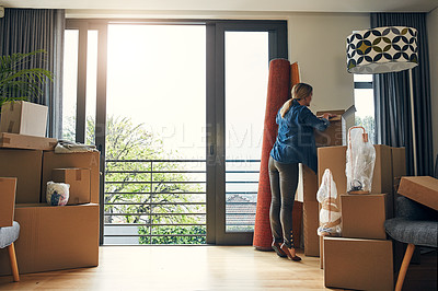 Buy stock photo Rearview shot of a focused middle aged woman packing out a box at her new home inside during the day