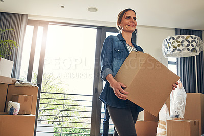 Buy stock photo Shot of a cheerful middle aged woman holding a box while moving into her new home inside during the day