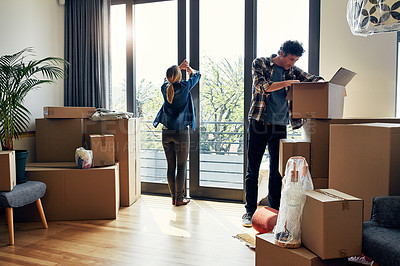 Buy stock photo Shot of a focused middle aged couple packing out a boxes at their new home inside during the day