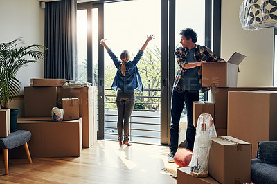 Buy stock photo Shot of a cheerful middle aged woman stretching her arms out on her balcony while her husband looks at her and packs out boxes on moving day