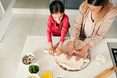Buy stock photo High angle shot of a middle aged mother and her daughter preparing a pizza to go into the oven in the kitchen at home