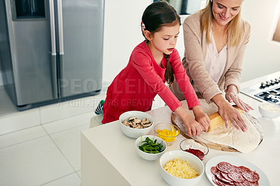 Buy stock photo Shot of a middle aged mother and her daughter preparing a pizza to go into the oven in the kitchen at home