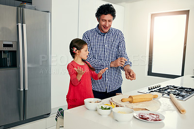 Buy stock photo Shot of a middle aged father and his daughter preparing a pizza to go into the oven in the kitchen at home