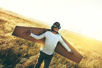 Buy stock photo Shot of a young boy pretending to fly with a pair of cardboard wings in an open field