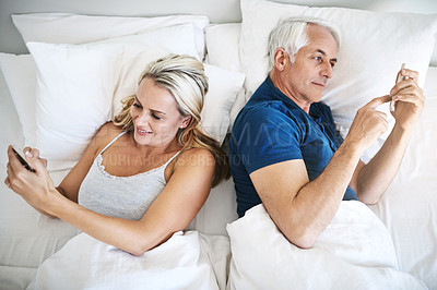 Buy stock photo Shot of a mature couple using their cellphones in bed at home