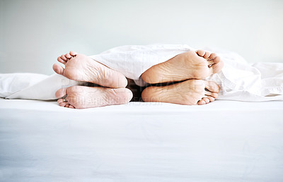 Buy stock photo Shot of a couple's bare feet sticking out underneath the bedsheets at home